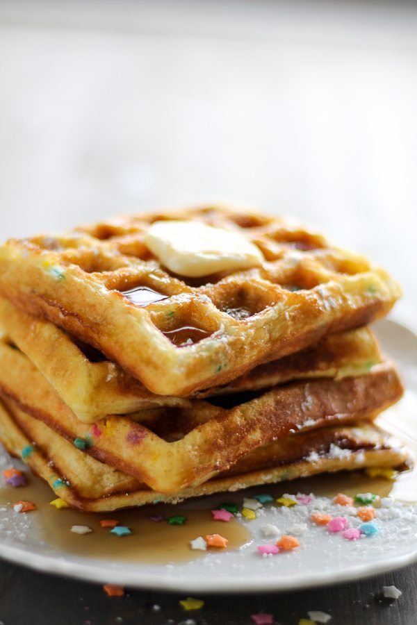 A stack of four cake waffles with funfetti, topped with melted butter and syrup