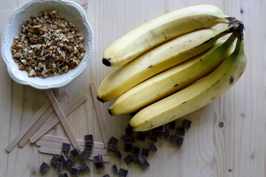 Bananas, dark chocolate chunks and chopped nuts on a wooden board