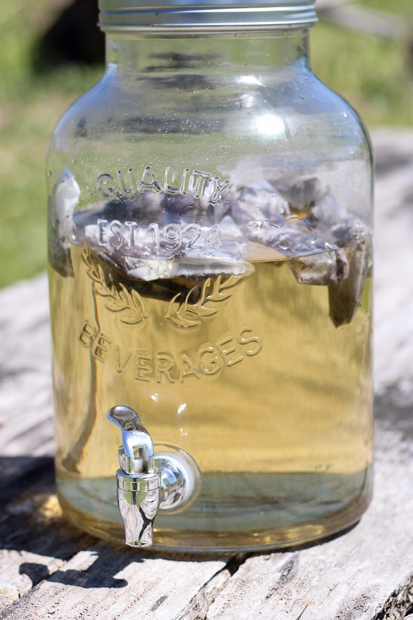 A Clear Glass Jug With Tea Bags Sitting In The Hot Sun