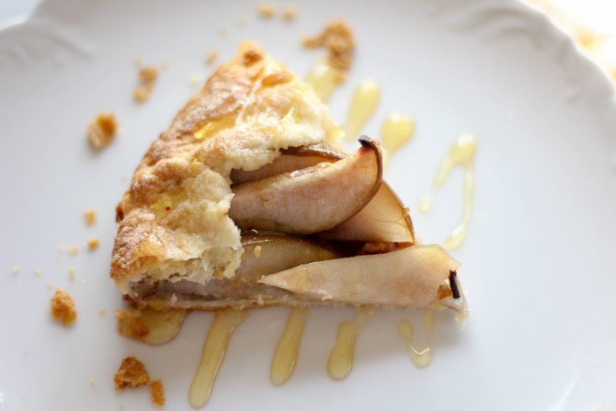a slice of a pear galette on a white plate, drizzled with honey