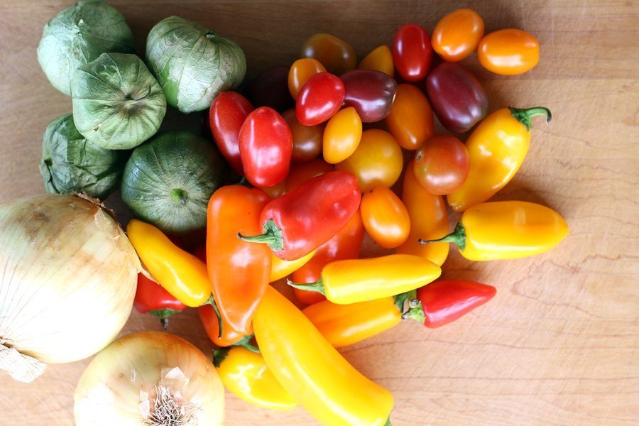 A variety of fresh vegetables on a wooden cutting board, cherry heirloom tomatoes, tomatillos, onions and sweet peppers