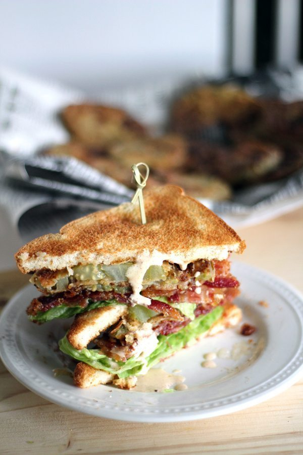 A white plate with a fried green tomato BLT sandwich with a plate of fried green tomatoes in the background
