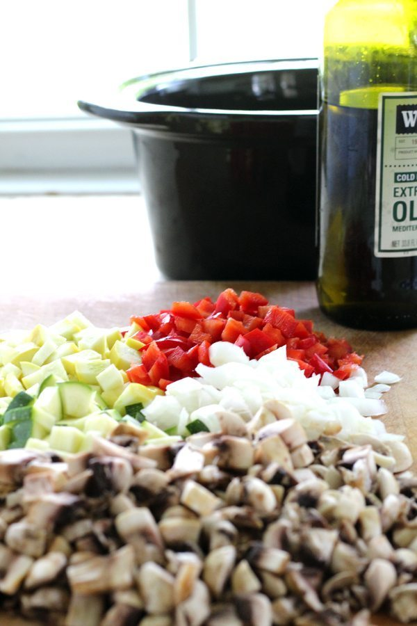 A cutting board with fresh chopped mushrooms, summer squash, zucchini, bell peppers and onions, with a crockpot in the background