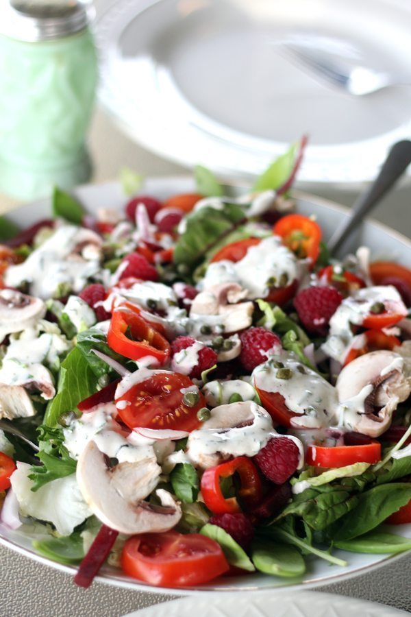 A platter filled with fresh greens, lettuce, peppers, raspberries, radishes and more