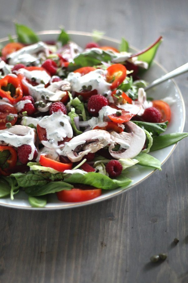 A large white plate with a salad topped with fresh raspberries,, mushrools, snow peas, radishes, peppers and more
