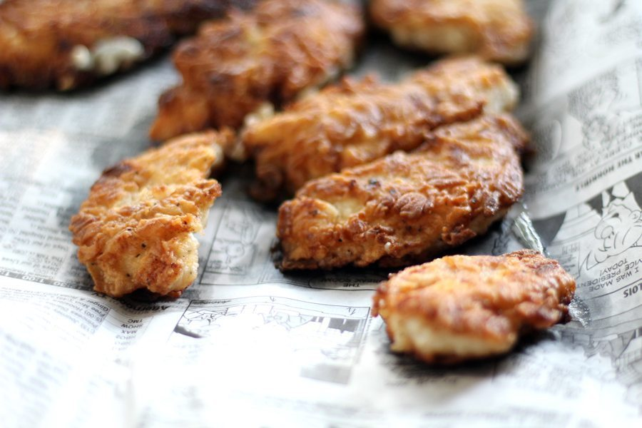 Tender strips of fried chicken draining on newspaper