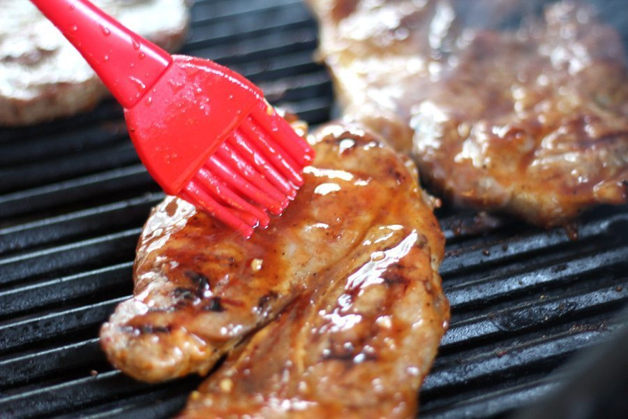 Sauce being brushed on grilled pork steaks.