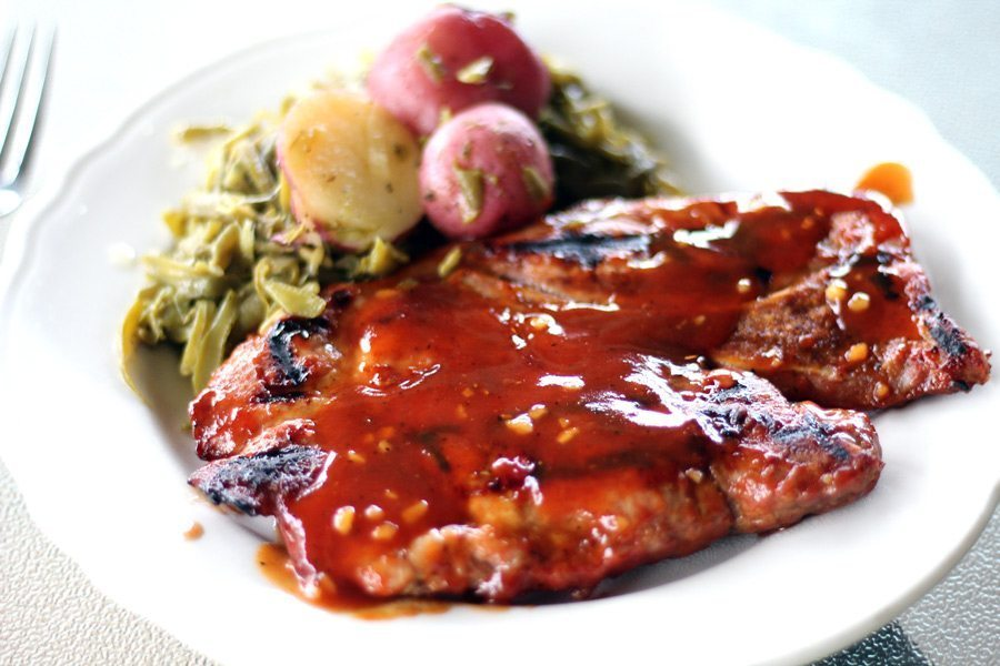 A pork steak with honey bourbon sauce, served on a plate with green beans and potatoes.