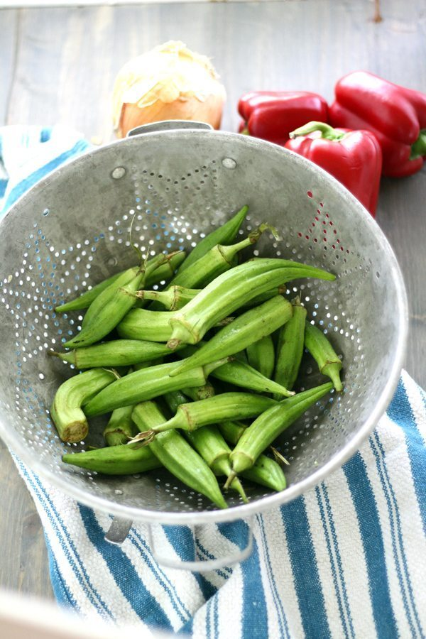 Garden fresh okra in a colander, with fresh bell peppers and vidalia onions in the background