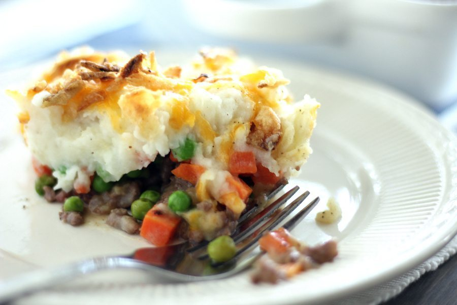 A helping of shepherds pie on a plate with a fork