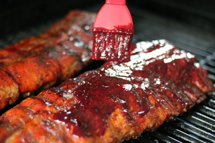 Blackberry BBQ sauce being brushed on to smoked grilled ribs