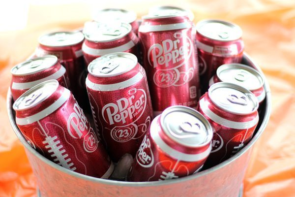 A metal tub full of Dr Pepper cans on ice