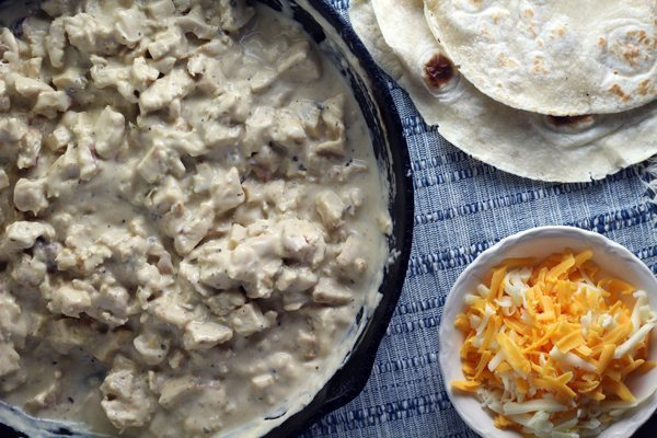 Chicken and cheese sauce combined in a skillet next to tortillas and a bowl of shredded mixed cheeses