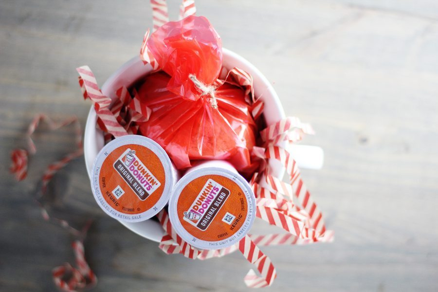 A coffee mug stuffed with shredded tissue paper, coffee and wrapped cookies for a gift