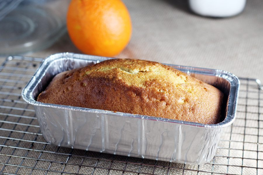 A baked pound cake cooling on a wire rack with an orange in the background