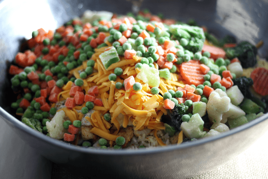 A bowl of frozen peas, carrots and other chicken rice casserole ingredients.