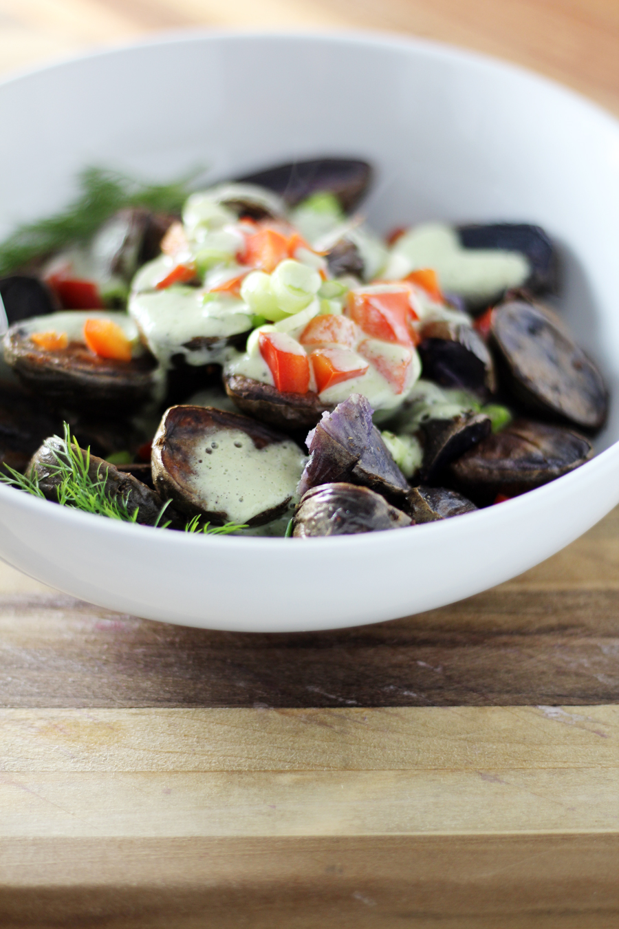 Sprinkle the purple potato salad with fresh chopped red bell peppers and green onions for added color and crunch.