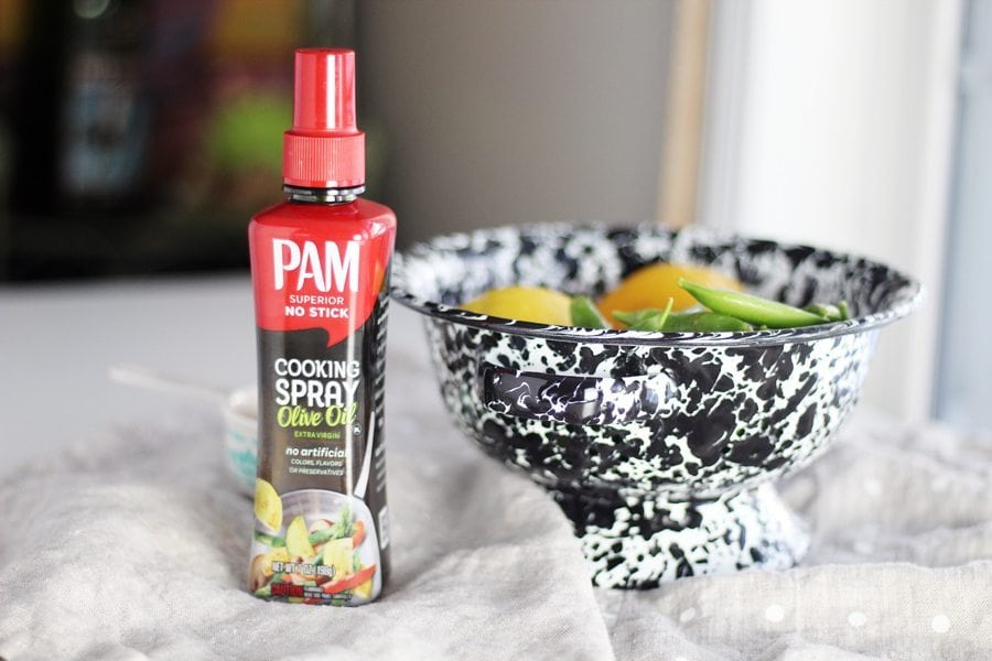 A bottle of PAM olive oil cooking spray next to a colander of vegetables