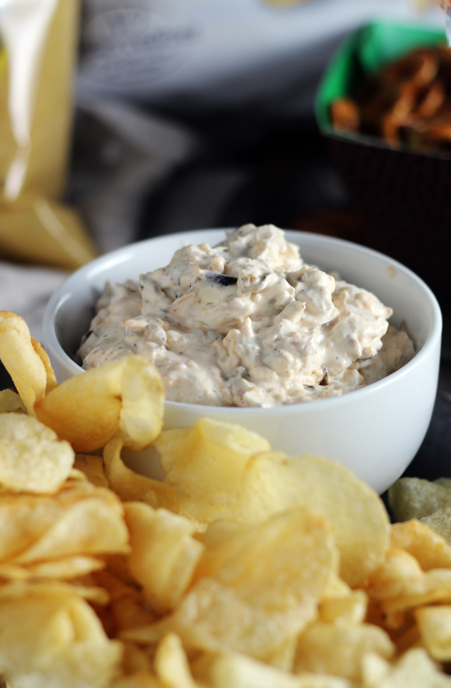 A bowl of sour cream + cheddar French onion dip next to kettle cooked potato chips