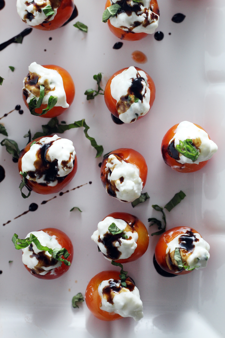 Tomato Basil Caprese Bites on a white serving platter drizzled with balsamic reduction