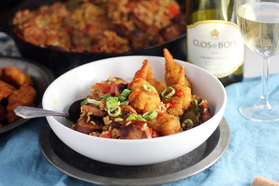 A bowl of shrimp jambalaya next to a glass of Chardonnay with a skillet in the background