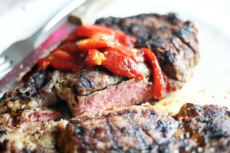 A medium rare ribeye topped with marinated sweet red peppers
