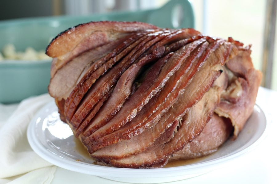 A honey glazed spiral baked ham on a white platter