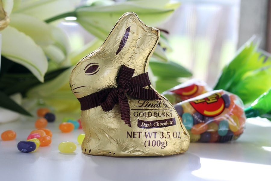 A gold wrapped dark chocolate Easter bunny with jelly beans and Easter lilies in the background
