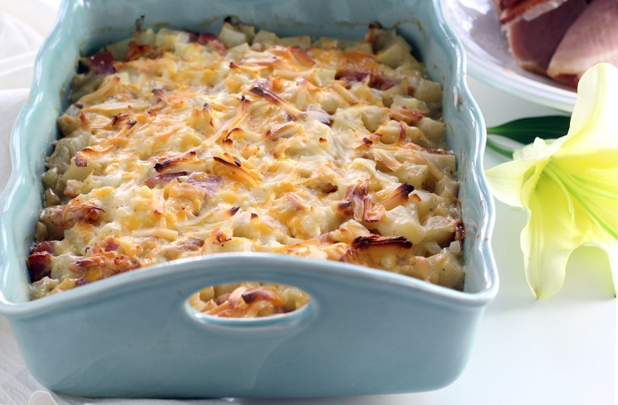 A potato ham casserole with cheese melted on top in a light blue baking dish