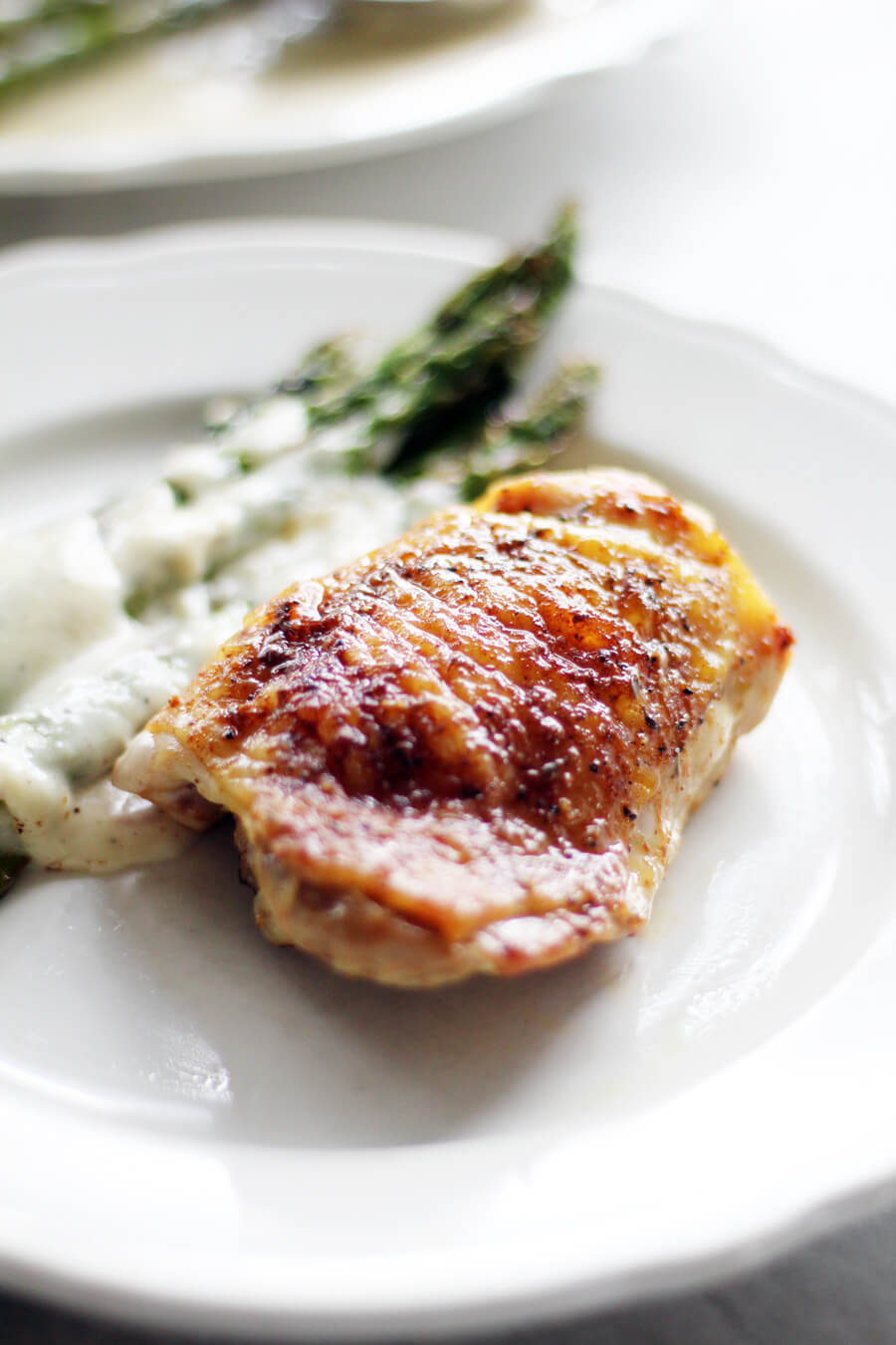A golden baked chicken thigh on a white plate next to asparagus