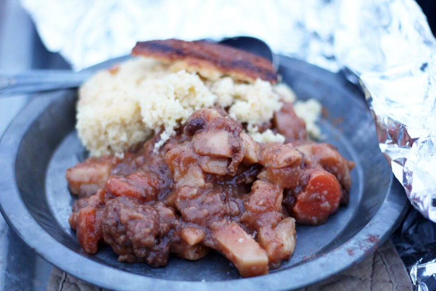 A metal plate with a helping of hot beef stew and skillet cornbread