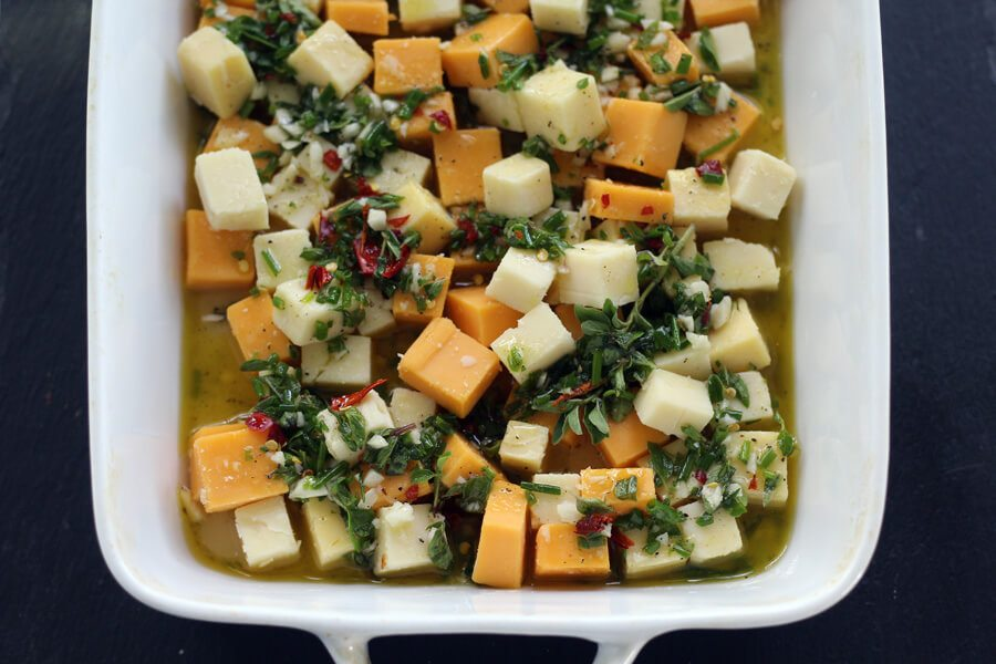 Cheddar cheese cubes in a white dish, covered with fresh herbs, olive oil and more