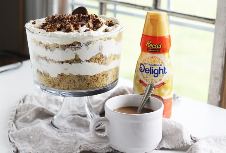 Peanut Butter Cup Punch Bowl Cake next to International Delight coffee creamer and a cup of coffee