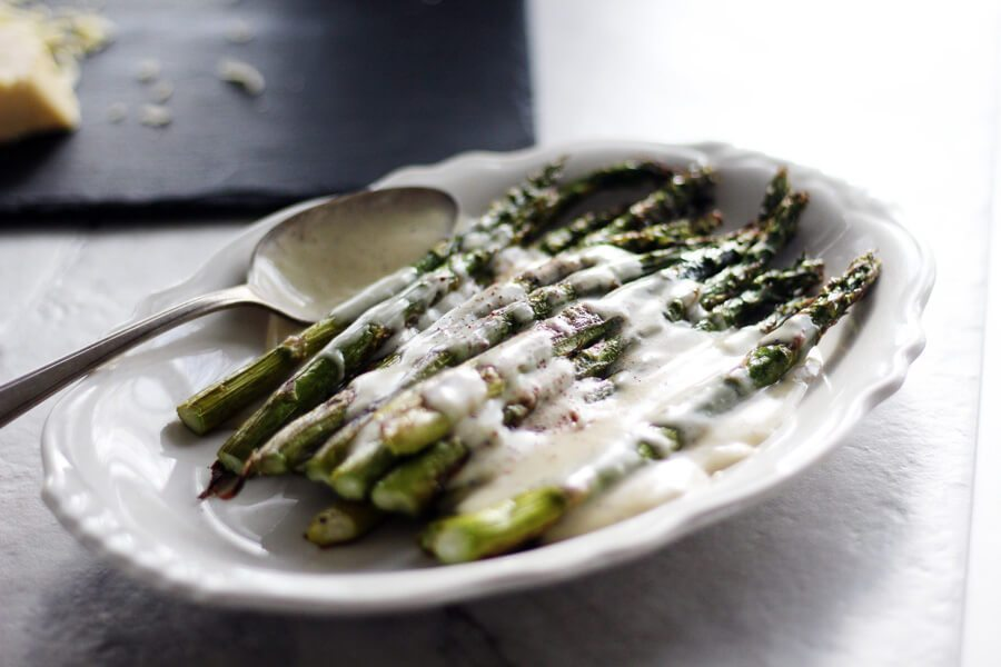 A plate of roasted asparagus, topped with cheese sauce next to a vintage spoon