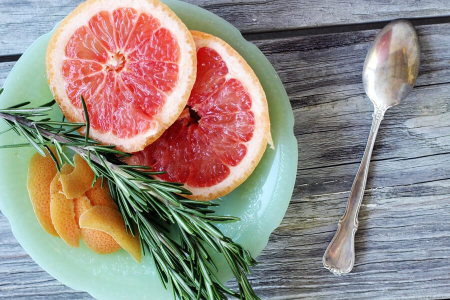 A small jade plate with slices of ruby red grapefruit, fresh rosemary and grapefruit peel