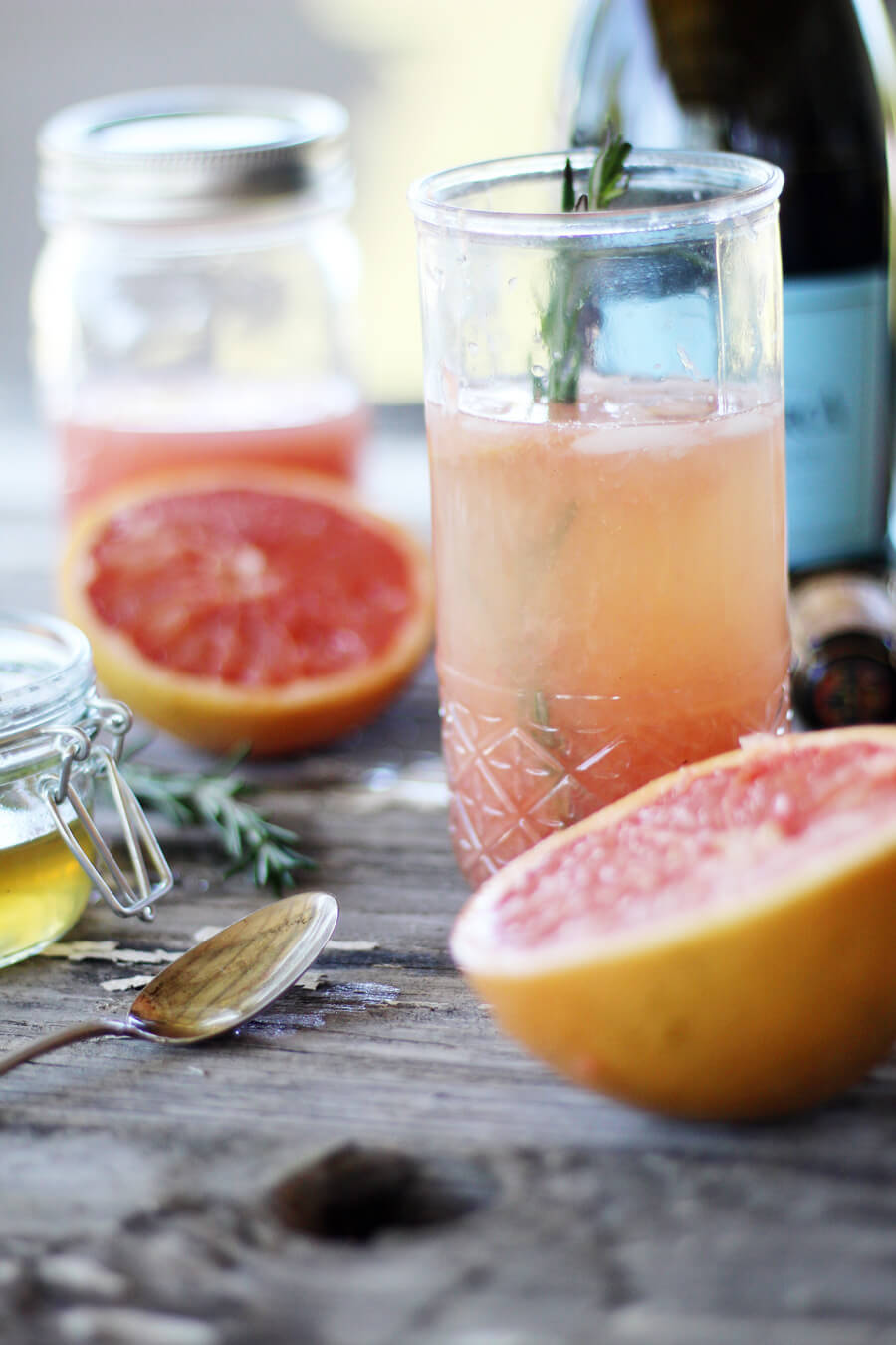 A grapefruit and prosecco cocktail next to a bottle, fresh sliced grapefruit and rosemary