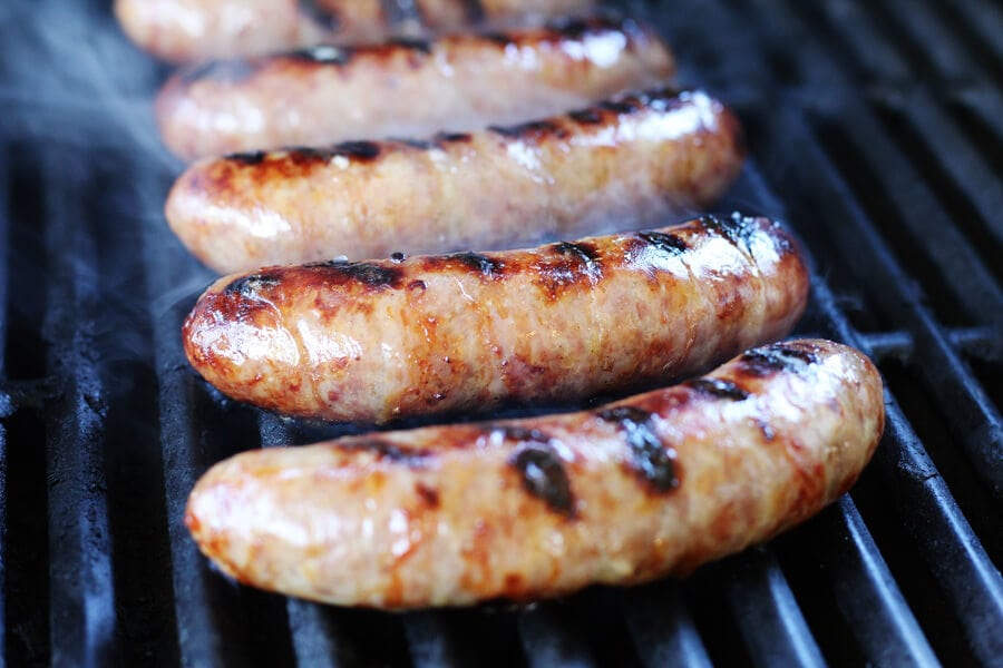 Beer bratwursts cooking on a hot grill