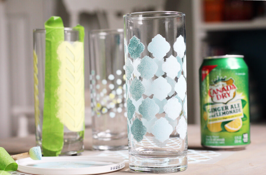 a close up shot of stenciled drinking glasses with a can of ginger ale in the background
