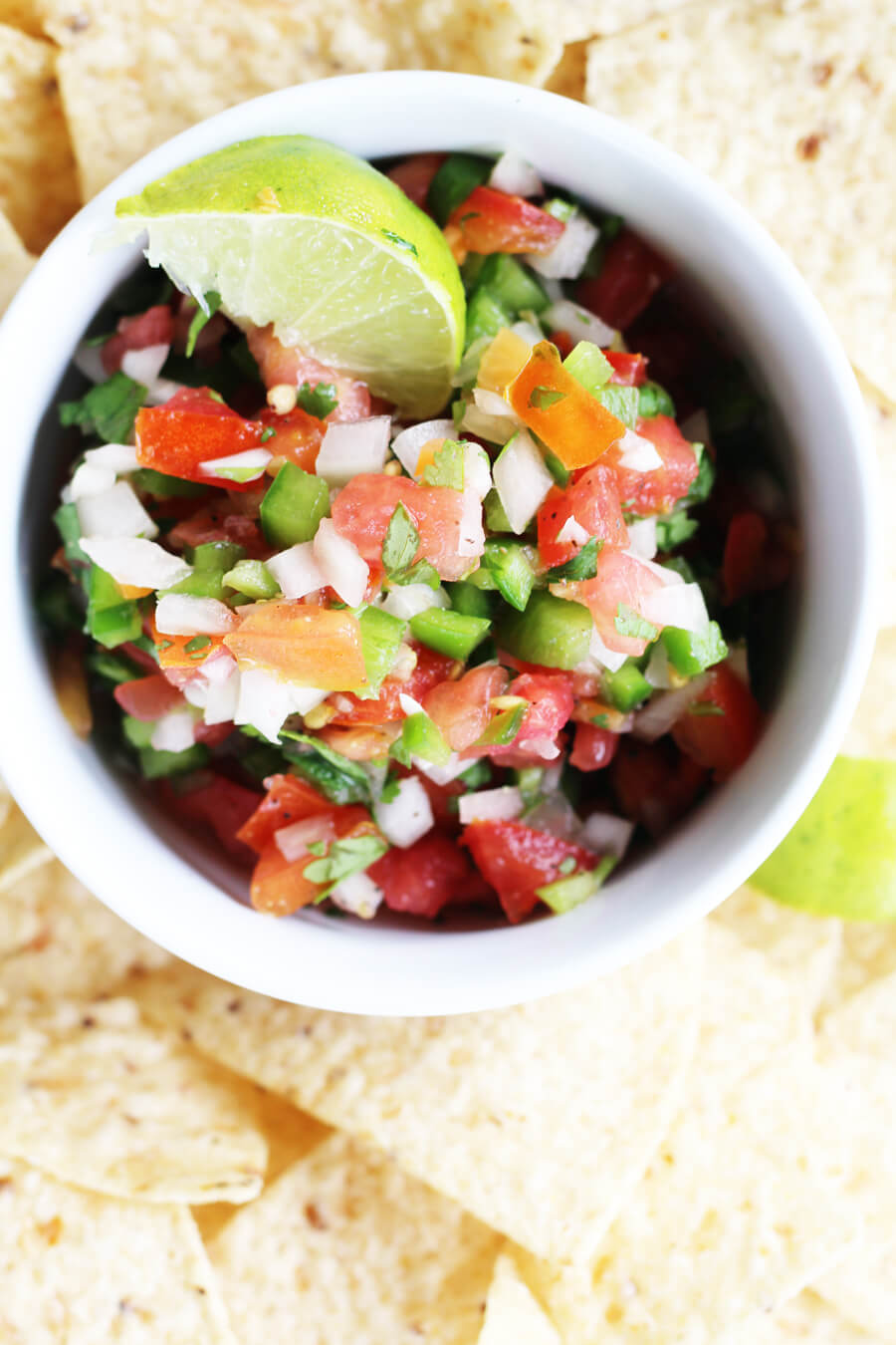 An overhead shot of freshly prepared tomato salsa next to crispty tortilla chips