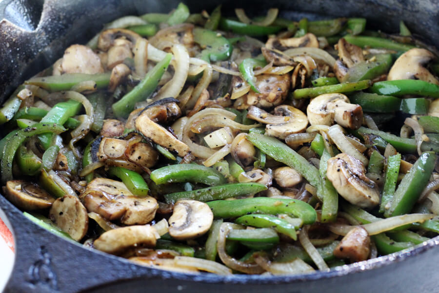 a cast iron skillet of slow simmered onions, mushrooms and bell peppers