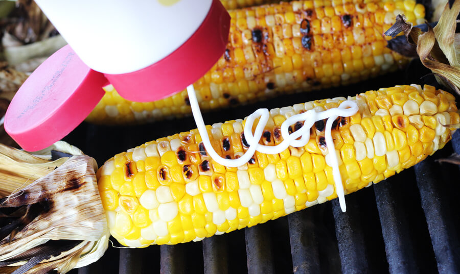 squeeze spread being added to a warm earn of corn on the grill