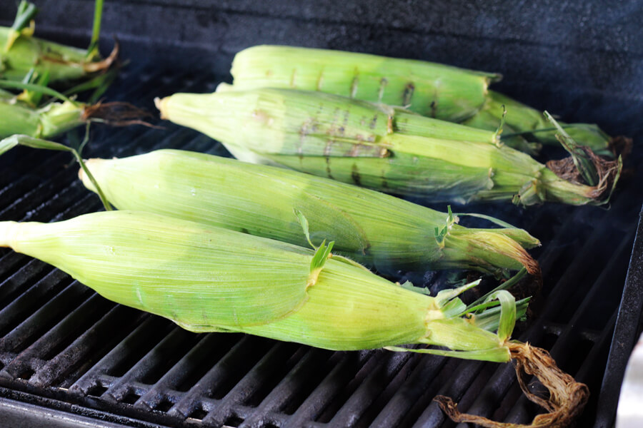 ears of fresh corn in the husk on a hot grill