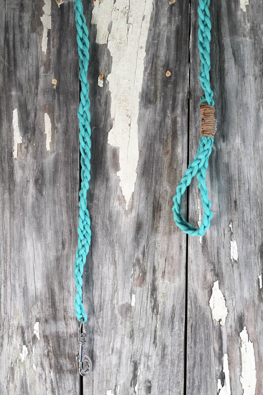 A teal blue rope dog leash drying on a wooden board