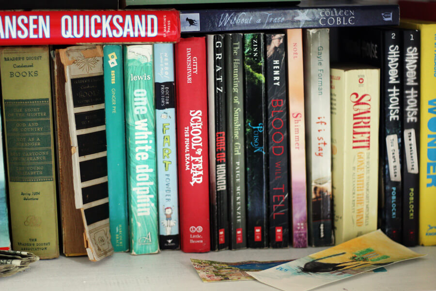 a bookshelf lined with various books, some new, some worn and tattered