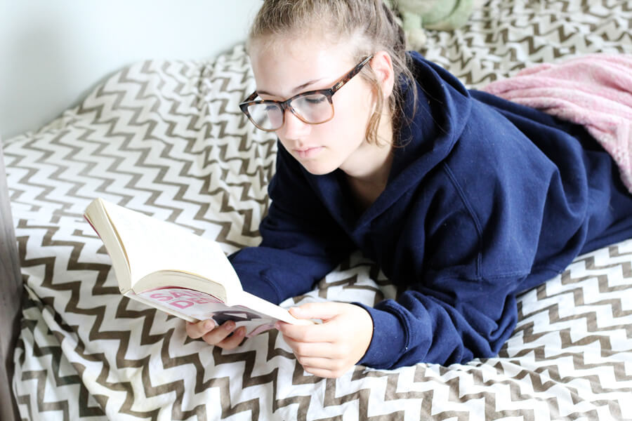 A girl with glasses lying on a bed reading a book