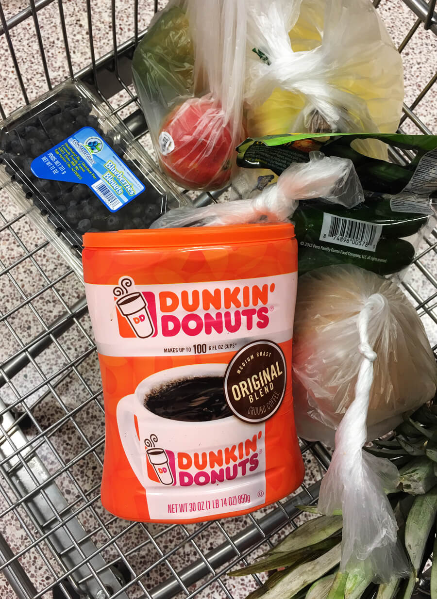 an overhead shot of Dunkin' Donuts coffee canister in a shopping buggy with other groceries from Publix
