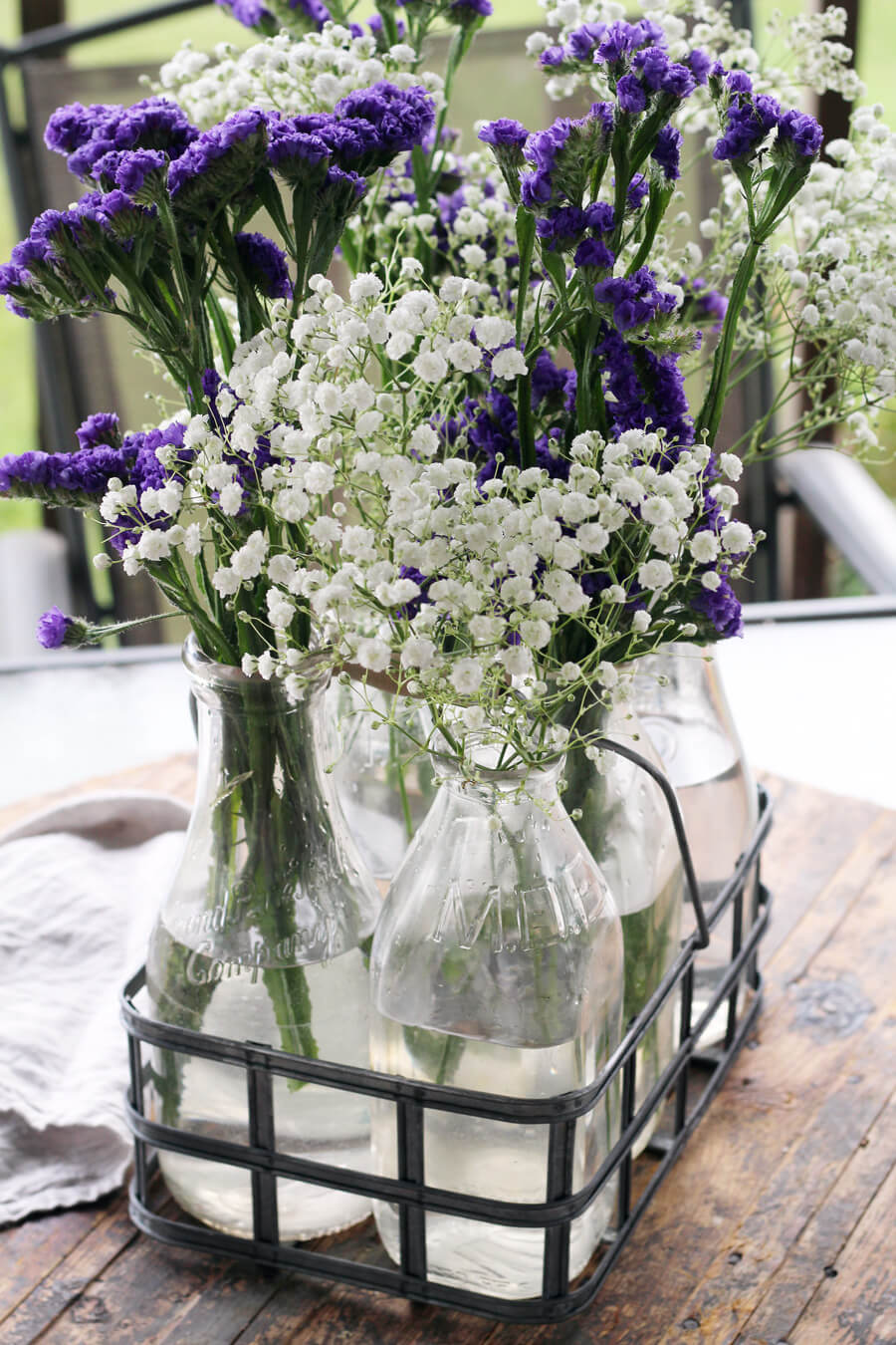 A flower arrangement of baby's breath and purple flowers in vintage milk bottles