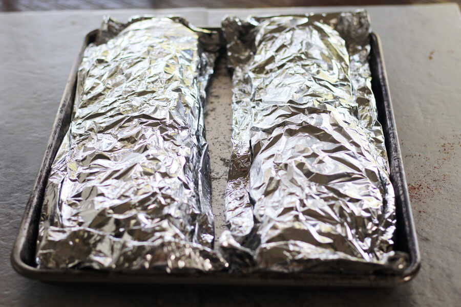 Two racks of ribs tightly wrapped in foil.