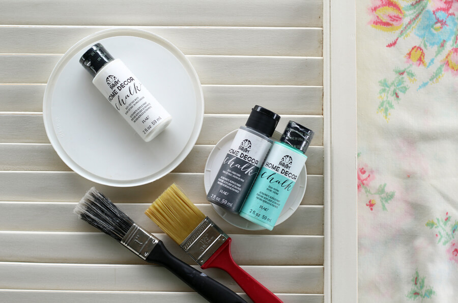 Paint, paint brushes, and supplies needed for this rustic wall decor project.