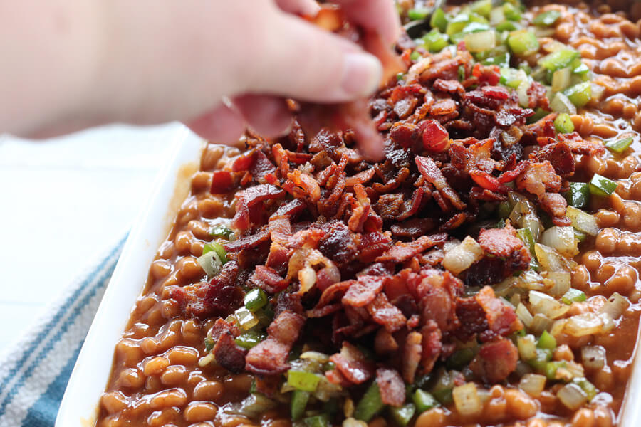 Cooked and crumbled bacon sprinkled on a dish of baked beans.